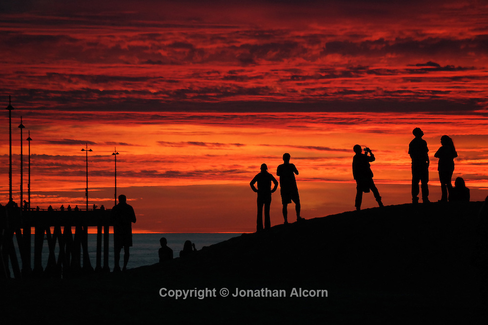 People gather to watch the sunset sky from a sand berm next to the Venice Beach pier.<br /> photo by Jonathan Alcorn