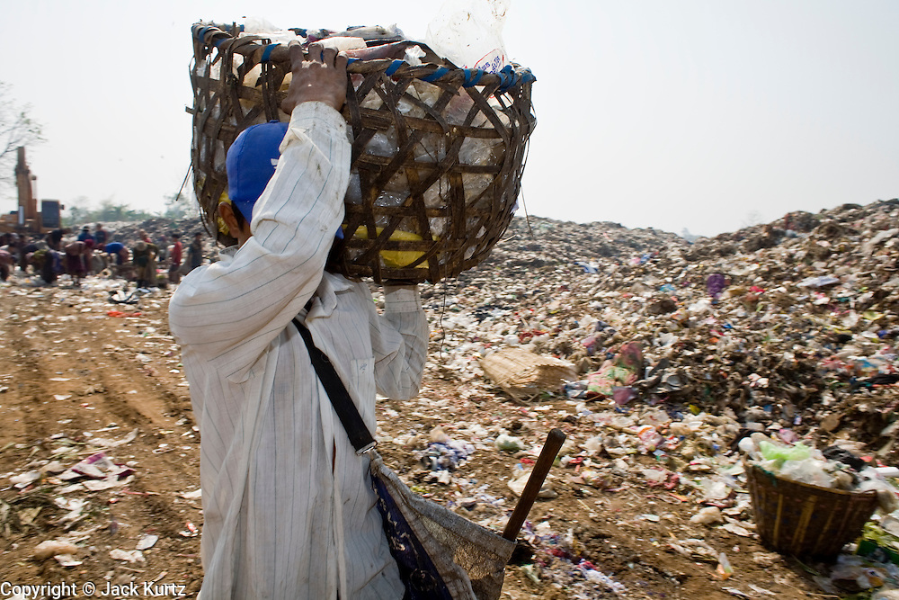 "25 FEBRUARY 2008 -- MAE SOT, TAK, THAILAND: Burmese refugees and migrants work in the landfill in Mae Sot, Thailand. There are millions of Burmese migrant workers and refugees living in Thailand. Many live in refugee camps along the Thai-Burma (Myanmar) border, but most live in Thailand as illegal immigrants. They don't have papers and can not live, work or travel in Thailand but they do so ""under the radar"" by either avoiding Thai officials or paying bribes to stay in the country. Most have fled political persecution in Burma but many are simply in search of a better life and greater economic opportunity.    PHOTO BY JACK KURTZ"