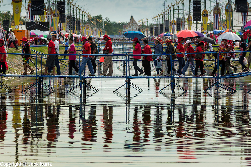 17 MAY 2014 - BANGKOK, THAILAND: Supporters of the Red Shirts cross a khlong (canal) to get to a Red Shirt rally in Bangkok. Thousands of Thai Red Shirts, members of the United Front for Democracy Against Dictatorship (UDD), members of the ruling Pheu Thai party and supporters of the government of ousted Prime Minister Yingluck Shinawatra are rallying on Aksa Road in the Bangkok suburbs. The government was ousted by a court ruling earlier in the week that deposed Yingluck because the judges said she acted unconstitutionally in a personnel matter early in her administration. Thailand now has no functioning government. Red Shirt leaders said at the rally Saturday that any attempt to impose an unelected government on Thailand could spark a civil war. This is the third consecutive popularly elected UDD supported government ousted by the courts in less than 10 years.    PHOTO BY JACK KURTZ