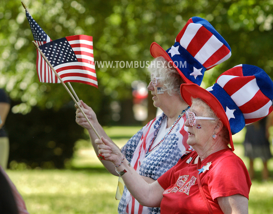 Middletown, New York - Two women wearing patriotic attire wave American flags during a Memorial Day ceremony on Monday, May 31, 2010.