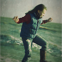 Young girl playing in the winter surf wearing wellington boots and gillet