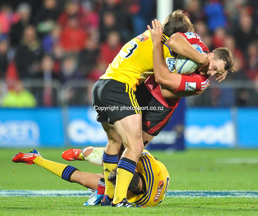 Israel Dagg of the Crusaders is tackled by Conrad Smith and Tim Bateman of the Hurricanes in the Super Rugby game, Crusaders v Hurricanes, 28 March 2014. Photo:John Davidson/photosport.co.nz