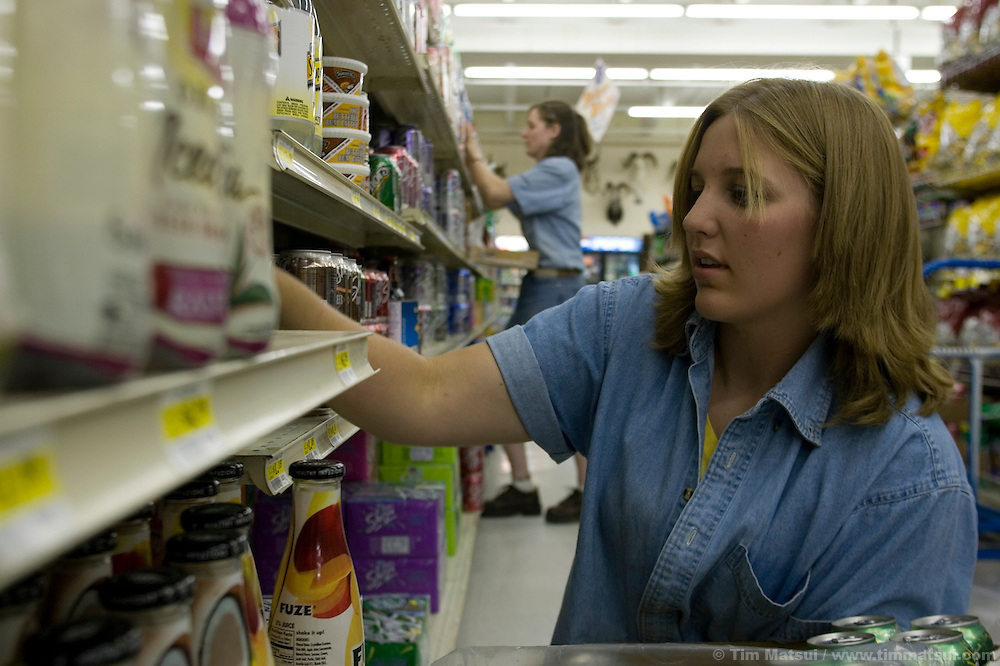 PINEDALE, WY - Sisters Heidi, 21, at left, and Sarah Pitchford, 16, at right, restock the shelves at Faler's, the only grocery store in Pinedale, Wy.,  (pop. 1400) on August 10, 2005, where the county assessor states average 2004 home sales were $200,000 and 2004 north Sublette county sales averaged $275,000. As the population of Pinedale grows many locals say it's hard to recognize familiar faces in frequented places like Faler's. Sublette County has 6400 permanent residents. Farms and ranches are being broken up and sold typically as two, five, 10, and 20 acre lots on septic systems and well water. One of the local sayings is that the escalating real estate prices are a result of the billionaires moving into nearby Jackson, WY, who are pushing out the millionaires who then move to Pinedale. According to realtor Travis Bing, anything one 'would want to buy' starts at about $200,000 with many homes selling for $450,000 and up. Pinedale currently has the lowest unemployment rate in the state and is experiencing another boom cycle both in real estate and in energy as natural gas production in two nearby gas fields ramps up for year-round production....NOTE: The Pitchfords essentially grew up in Pinedale. There father is a pastor at the Emmanuel Baptist church. Sarah wants to go to college for sports medicine, Heidi is in school for biblical languages.