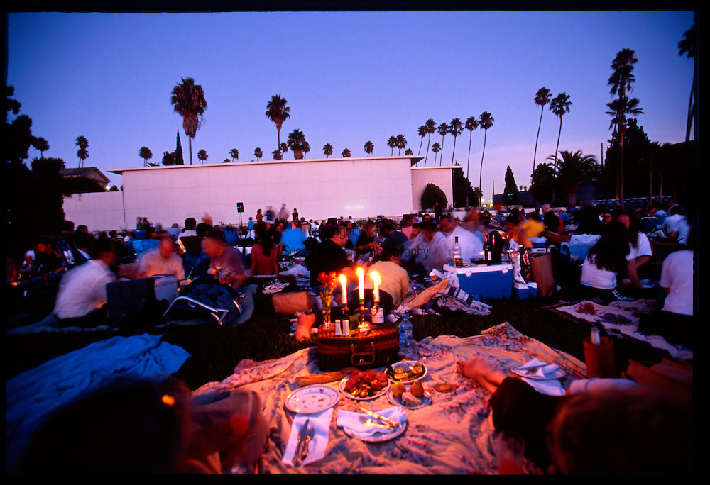 Cinespia features mid-century movies projectd on to the wall of the marble mausoleum wall.  People who attend are encouraged to bring a picnic supper, blanketsand wine as they watch the movies outside, under the stars and among the graves and headstones.