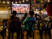 19 NOVEMBER 2018 - BANGKOK, THAILAND: People watch a movie outside projected across the canal during the Loy Krathong Fair along Klong (Canal) Ong Ang in Bangkok. This the first public event along the canal. Businesses that line the canal weve evicted about two years and the walkways along the canal were renovated. Loy Krathong takes place on the evening of the full moon of the 12th month in the traditional Thai lunar calendar. In the western calendar this usually falls in November. Loy means 'to float', while krathong refers to the usually lotus-shaped container which floats on the water. Traditional krathongs are made of the layers of the trunk of a banana tree or a spider lily plant. Now, many people use krathongs of baked bread which disintegrate in the water and feed the fish. A krathong is decorated with elaborately folded banana leaves, incense sticks, and a candle. A small coin is sometimes included as an offering to the river spirits. On the night of the full moon, Thais launch their krathong on a river, canal or a pond, making a wish as they do so. The krathongs made at the Klong Ong Ang fair were made out of bread so they would decompose and feed the fish in the canal. Loy Krathong will be celebrated on November 22 this year.     PHOTO BY JACK KURTZ