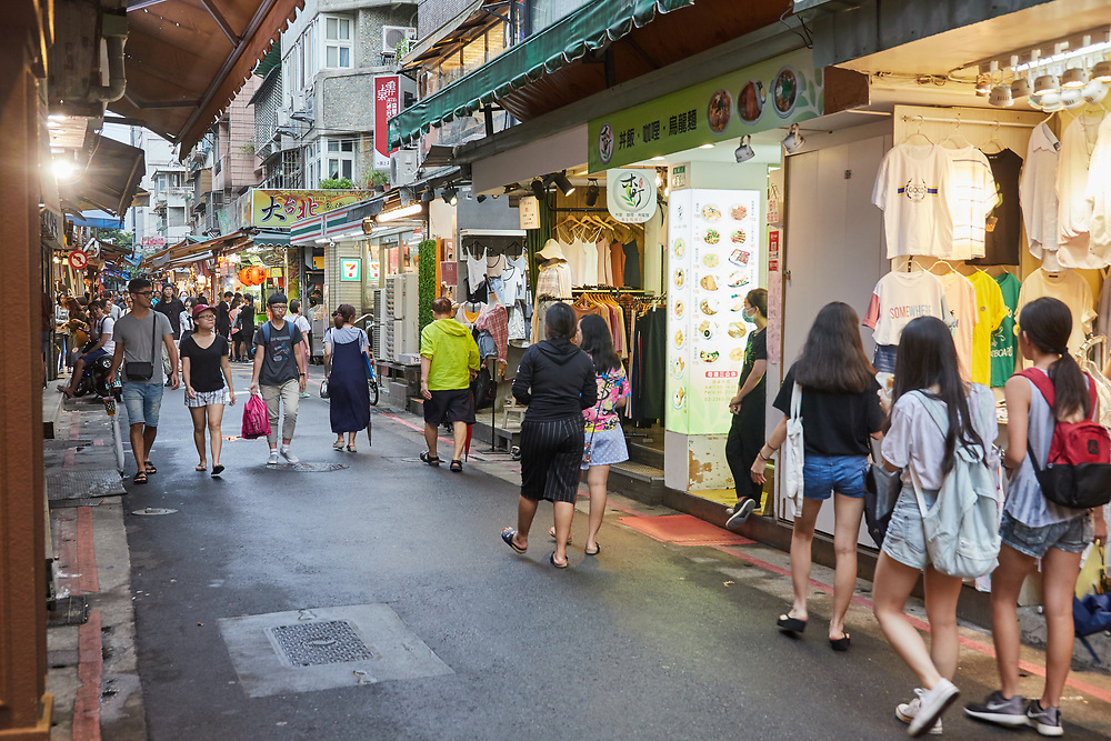 Tourists and locals enjoying an early evening walk around Shida night market. The lanes and alleys that make up the market are filled with street food stalls, boutiques and gift shops.