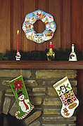 mantlepiece over stone fireplace, Christmas stockings & decorations