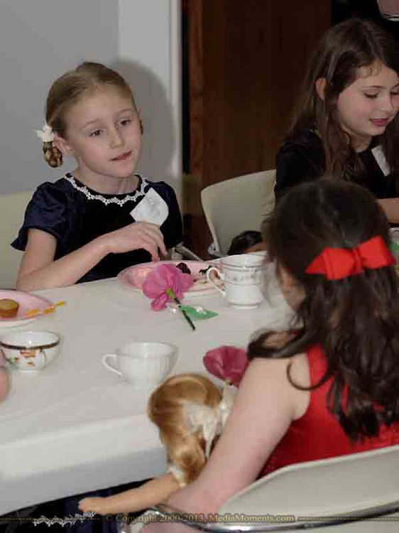 Elizabeth Brown, 8 (left,) who attends Waynesville Elementary, talks to Kayla Coffman, 9 (in red) at the American Girl Tea Party, Saturday, January 27, 2007 in Waynesville's Mary L. Cook Library.