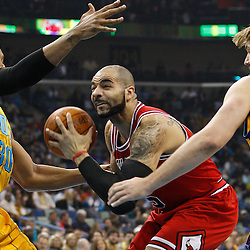 February 12, 2011; New Orleans, LA, USA; Chicago Bulls power forward Carlos Boozer (5) drives between New Orleans Hornets power forward David West (30) and New Orleans Hornets center Aaron Gray (34) during the first quarter at the New Orleans Arena.   Mandatory Credit: Derick E. Hingle