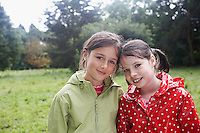 Portrait of two girls (7-9) in raincoats