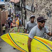 "Lead by ""Bocão"", young surfers inside the Rocinha's slum narrow streets"