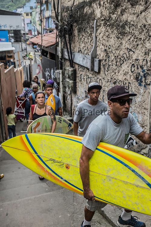 """Lead by """"Bocão"""", young surfers inside the Rocinha's slum narrow streets"""