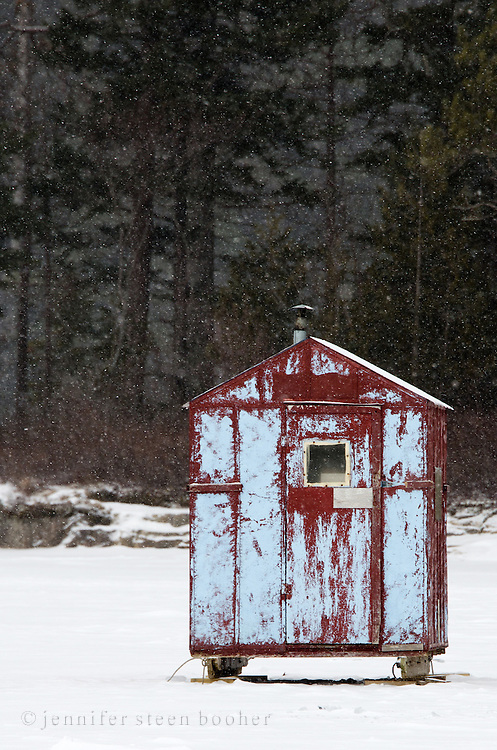 A battered red and blue ice fishing shack in a snowstorm.