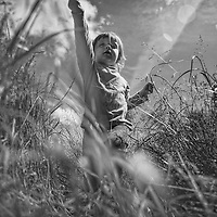 A girl running through long grass viewed from below looking up on summers day