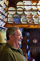 Standing among the collection of plates secured to the wall of the Snake Pit's dining area, Peak reminisces about the customers and friends he's met while operating the eatery since 1978.