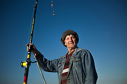 © Licensed to London News Pictures. <br /> 12/10/2014. <br /> <br /> Saltburn, United Kingdom<br /> <br /> Tony Savage, a fisherman from Marske poses for a picture during the annual Jim Maidens memorial beach fishing competition in Saltburn by the Sea in Cleveland. <br /> The competition is held each year to mark the death of Saltburn plumber and keen fisherman Jim Maidens who died in 1998 when he was killed after being swept overboard from his boat 'Corina' close to the beach at Saltburn.<br /> <br /> Photo credit : Ian Forsyth/LNP