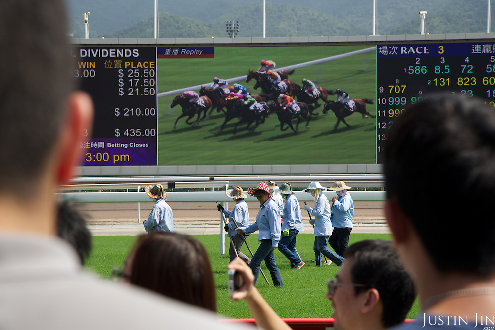 Workers prepare the track at the Hong Kong Jockey Club's Shatin Racecourse.