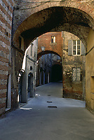 Arches of buildings over street Siena Italy