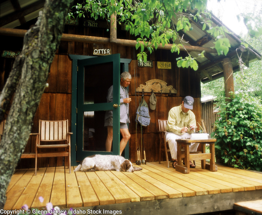 Tying flies for flyfishing on porch of cabin w/ sleeping dog, Selway  Lodge, Idaho. MR