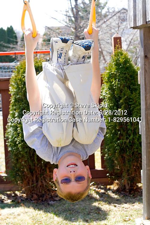 Boy age 12 playing on backyard swing set exercise rings. St Paul Minnesota MN USA