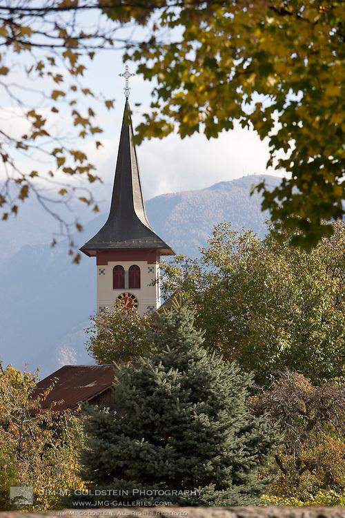 Church clock tower seen through fall colored trees in Steg, Switzerland