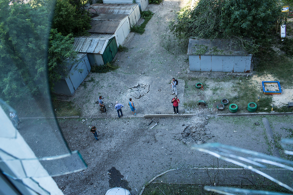 Journalists and local residents, along with two impact craters, are visible out of a window broken by suspected grad rocket strikes outside an apartment building on Tuesday, July 29, 2014 in Donetsk, Ukraine.