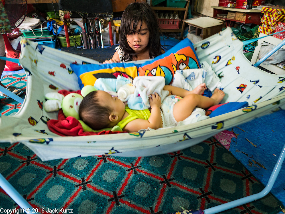 07 APRIL 2016 - BANGKOK, THAILAND: A girl watches her baby brother in their home in the Mahakan Fort squatters' community. Mahakan Fort was built in 1783 during the reign of Siamese King Rama I. It was one of 14 fortresses designed to protect Bangkok from foreign invaders, and only of two remaining, the others have been torn down. A community developed in the fort when people started building houses and moving into it during the reign of King Rama V (1868-1910). The land was expropriated by Bangkok city government in 1992, but the people living in the fort refused to move. In 2004 courts ruled against the residents and said the city could take the land. The final eviction notices were posted last week and the residents given until April 30 to move out. After that their homes, some of which are nearly 200 years old, will be destroyed.       PHOTO BY JACK KURTZ