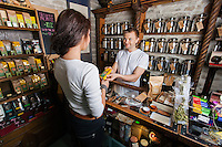Salesperson giving product to female customer in tea store
