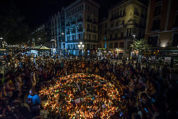 August 18, 2017 - Barcelona, Catalonia, Spain - People gather around a makeshift memorial on top of the Joan Maro mosaic in Las Ramblas, the site where a van came to a halt after a 550 meter long jihadist terror trip. Thirteen people were killed and almost 80 wounded, 15 seriously, when the van tore through the crowd (Credit Image: © Matthias Oesterle via ZUMA Wire)