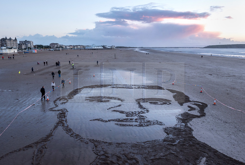 """© Licensed to London News Pictures. 11/11/2018. Weston-super-Mare, North Somerset, UK. Pages of the Sea on the Armistice Day centenary, 1918-2018, of the end of the First World War. Pictured: a sand portrait of Lieutenant Colonel John Hay Maitland Hardyman, designed by sand artists Sand In Your Eye,  drawn into the sand on Weston's beach to be washed away as the tide comes in. Lieutenant Colonel John Hay Maitland Hardyman, D.S.O. M.C. (28 September 1894 – 24 August 1918) was born in Bath, was an Officer in the Royal Flying Corps and was awarded for gallantry. In May 1918, aged only 23, he became the youngest lieutenant colonel in the British Army. In December 1914, he was accepted for officer training with the Royal Flying Corps (forerunner of the RAF) at Brooklands, Surrey, though eventually served with the Somerset Light Infantry. He was awarded the Distinguished Service Order for conspicuous gallantry and devotion to duty. After the enemy had penetrated allied lines, John went forward through a heavy barrage to rally the troops and repel repeated enemy attacks over two days and three nights. He encouraged them through """"coolness and absolute disregard of personal danger"""" to maintain a tactically important position. He was killed in action at Bienvillers, France, and buried in the military cemetery there. He was killed in France aged 24. Pages of the sea was devised by film-maker Danny Boyle and held at over 30 beaches across the UK on 11th November. Each event centres around a drawing of a large-scale portrait of a casualty from the First World War, designed by local sand artists, which will be washed away as the tide comes in.<br /> Photo credit: Simon Chapman/LNP"""