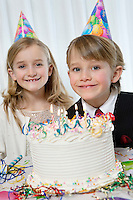Portrait of happy birthday boy with sister and cake