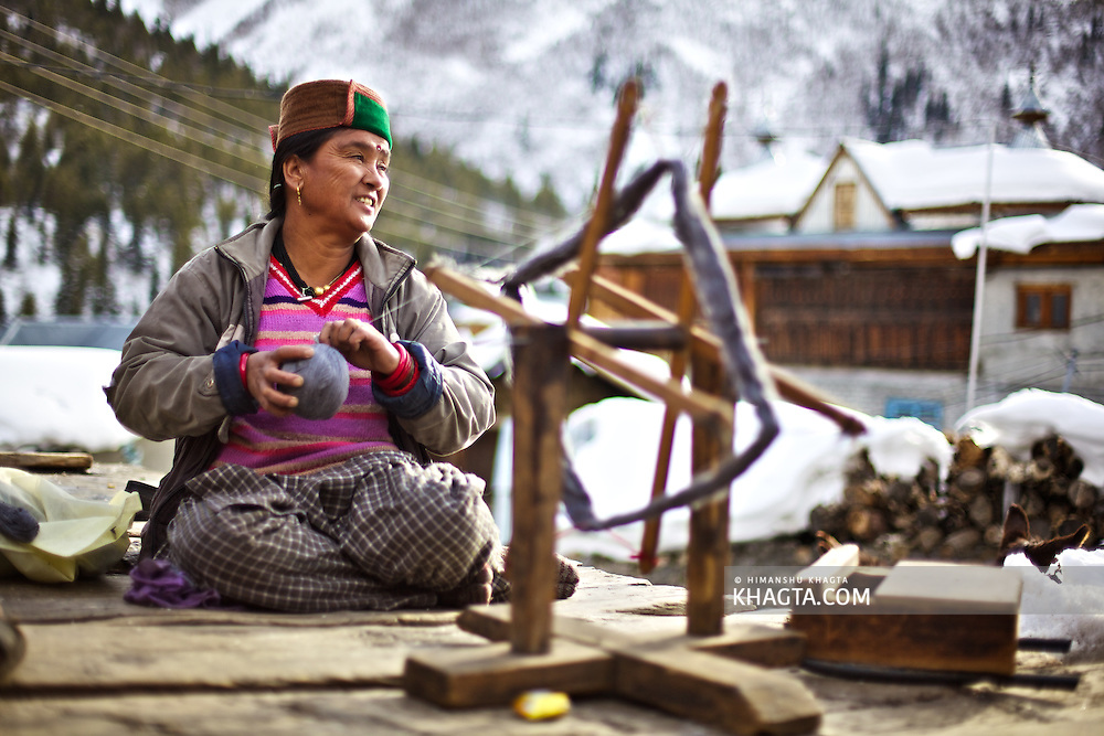 A lady spins wool outside her home in village Chikul, Sangla, Kinnaur in the cold winters. The village remains cutof from the outside world in winters so the villagers spend there days by making hand made woolen garments.
