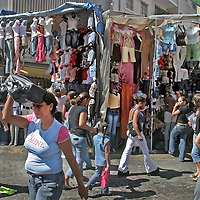 "Buhoneros - Pedestrians pass buhoneros' stalls filled with goods in the Sabana Grande neighborhood of Caracas Friday, December 15, 2006.  Buhoneros, thousands of workers who sell products from clothing and accessories to household goods and bootleg DVDs, make up the controversial ""informal economy.""  While many Caracas residents complain that the buhoneros have taken over streets with their makeshift marketplace, many buhoneros give thanks to Venezuelan President Hugo Chavez for allowing them a way to survive by creating their own small businesses."