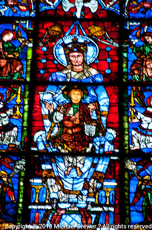 Our Lady of Chartres Cathedral, Chartres, France. Detail of the 12th century window La Belle Verrière. It is probably the most famous at Chartres, found in the first bay of the choir after the south transept. This part shows the Virgin and child surrounded by adoring angels and dates from around 1180.  The Virgin is depicted wearing a blue robe and sitting on a throne, with the Christ Child seated on her lap, raising his hand in blessing. This composition, known as the Sedes sapientia ('Throne of Wisdom',) is based on the famous cult figure kept in the crypt.