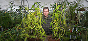 Botany professor Ken Cameron shows off 2 vanilla orchids. (Photo © Andy Manis)