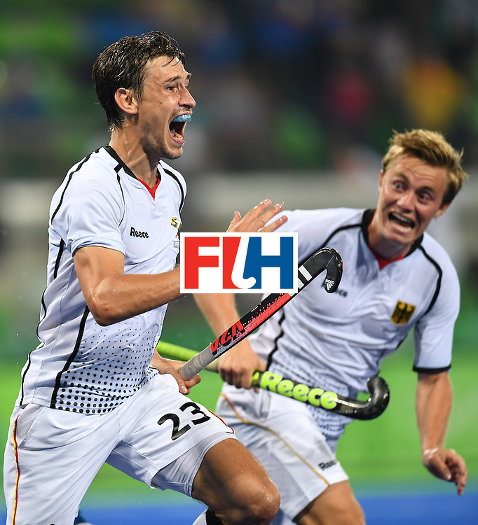 Germany's Florian Fuchs (L) celebrates his team's third goal during the men's quarterfinal field hockey Germany vs New Zealand match of the Rio 2016 Olympics Games at the Olympic Hockey Centre in Rio de Janeiro on August 14, 2016. / AFP / MANAN VATSYAYANA        (Photo credit should read MANAN VATSYAYANA/AFP/Getty Images)