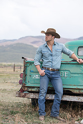 hot cowboy leaning on an old truck
