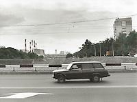 En russisk Zhiguli kjører på motorveien i Moskva. Fotografiet er printet på tradisjonell måte i mørkerom og deretter håndkolorert.<br /> Foto: Svein Ove Ekornesvåg