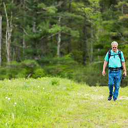 A man birdwatching in a field in York, Maine.