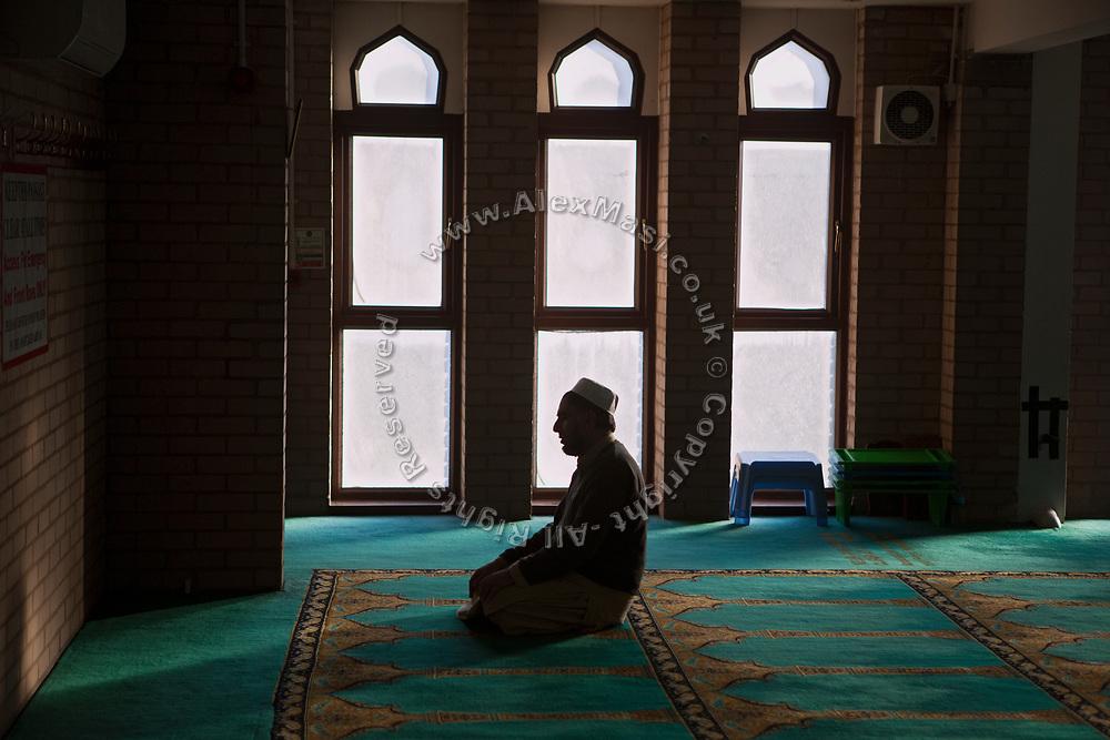 A muslim man is praying in Birmingham Central Mosque.