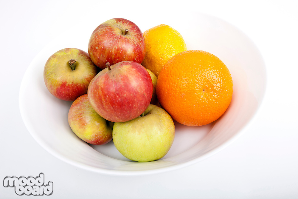 Fresh fruits in plate against white background