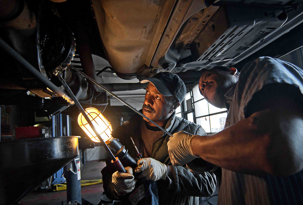 District of Colombia -Elliot Menovo, owner of a automobile repair shop located on Georgia Avenue, and his assistant mechanic repair the rear differentials of a taxi cab.  Photo by Erika Barker