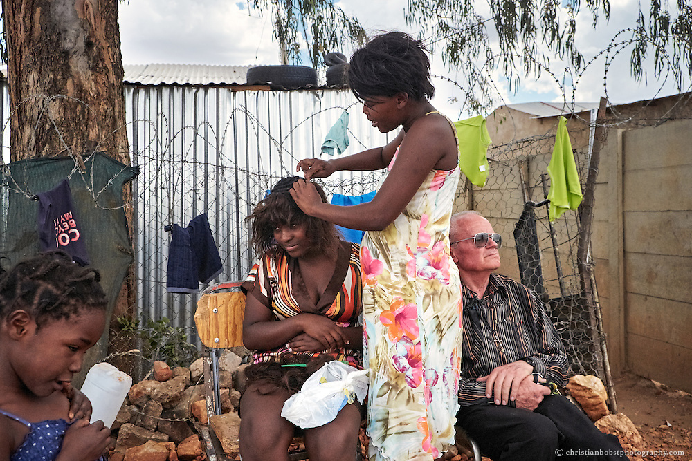 Damara 6, Katutura township (Windhoek), November 27, 2013. Father Hermann rests while some girls are doing their hair. It took a few years until the women started to trust the priest. But now many say that he is like a real father to them. He became part of the family, part of the people in the township.