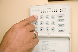 Close up of hand of older man setting his house alarm,