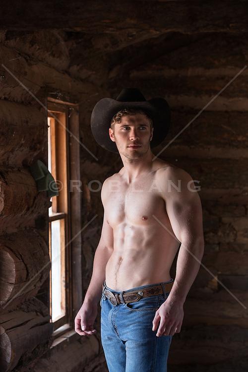 shirtless cowboy inside a cabin