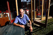 Jeremy Sims, 48, is portrayed in front of his house in BedZED on Thursday, Sep. 6, 2007. BedZED or the Beddington Zero Energy Development, is an environmentally-friendly housing development near Wallington, England in the London Borough of Sutton. It was designed by the architect Bill Dunster who was looking for a more sustainable way of building housing in urban areas in partnership between the BioRegional Development Group and the Peabody Trust. There are 82 houses, 17 apartments and 1,405 square meters of work space were built between 2000. The project was shortlisted for the Stirling Prize in 2003. The project is designed to use only energy from renewable source generated on site. In addition to 777 square meters of solar panels, tree waste is used for heating and electricity. The houses face south to take advantage of solar gain, are triple glazed and have high thermal insulation while most rain water is collected and reused. Appliances are chosen to be water efficient and use recycled water wherever possible. Low impact building materials were selected from renewable or recycled sources and were all originating within a 35 mile radius of the site to minimize the energy required for transportation. Also, refuse collection facilities are designed to support recycling and the site encourage eco-friendly transport: electric and LPG cars have priority over petrol/diesel cars, and electricity is provided by parking spaces appositely built for charging electric cars.