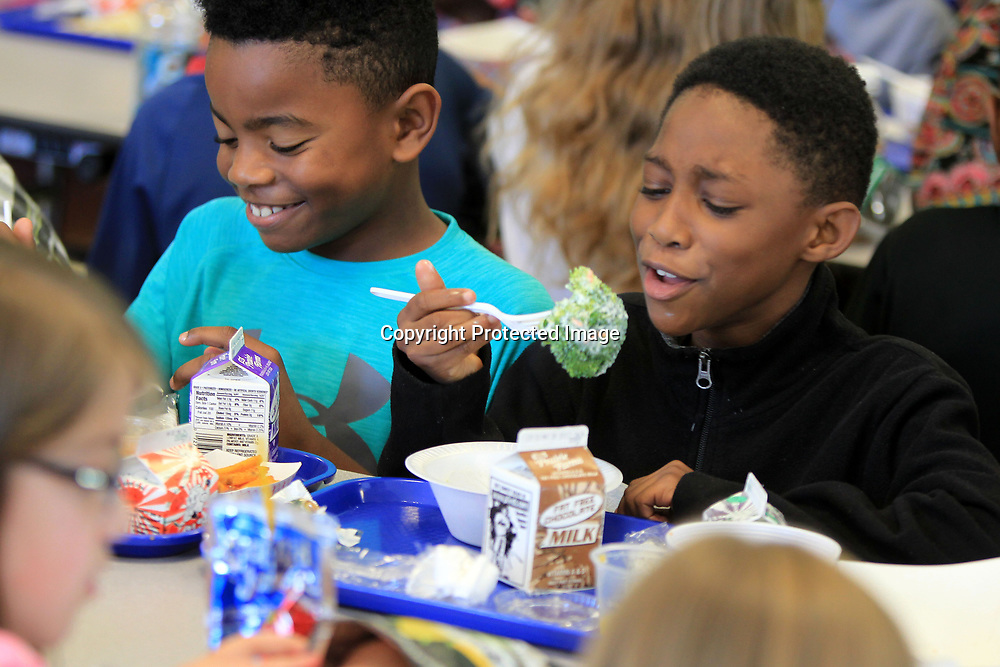 Landon Swinney, left, gets a laugh from his classmate Zuriel White, both 8, and second graders at Joyner Elementary School, as White attempts to eat a large stalk of broccoli from his salad during lunch on Tuesday. Students at Joyner were able to eat at the school's new salad bar at lunch. The salad bar is a part of a larger effort by the Tupelo Public School District to make healty habits part of students everyday lives.
