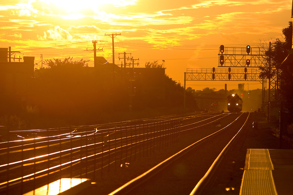 Rushing out of the setting sun, a Chicago-bound Metra train approaches the Grand/Cicero stop on the Milwaukee West Lines.