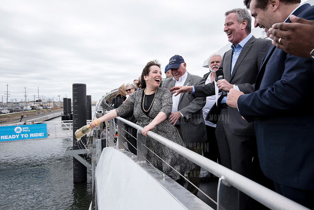 April 30, 2017 - New York, NY : New York City Mayor Bill de Blasio kicked off the city's new ferry service with a ceremonial first ride from  the Rockaways to lower Manhattan on Sunday, April 30.  Here, Laura Deckelman, a Rockaway resident and photographer, center, christens the ferry Urban Journey with a bottle of sprakling wine on Sunday morning. The Mayor is visible second from right.  CREDIT: Karsten Moran for The New York Times