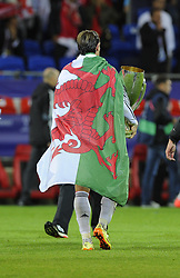Real Madrid's Gareth Bale leaves the pitch with the Uefa Super Cup draped in a Welsh Flag - Photo mandatory by-line: Joe Meredith/JMP - Mobile: 07966 386802 12/08/2014 - SPORT - FOOTBALL - Cardiff - Cardiff City Stadium - Real Madrid v Sevilla - UEFA Super Cup